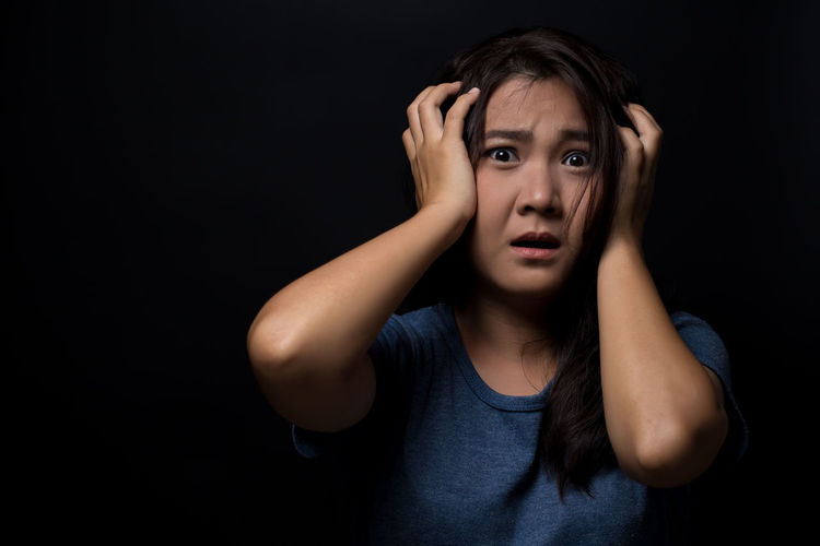 Portrait Of Scared Young Woman Standing Against Black Background