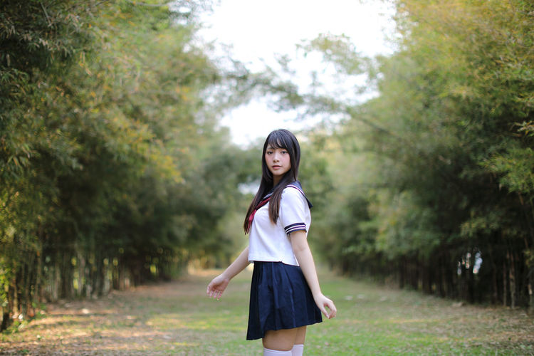 Portrait of young woman standing against trees