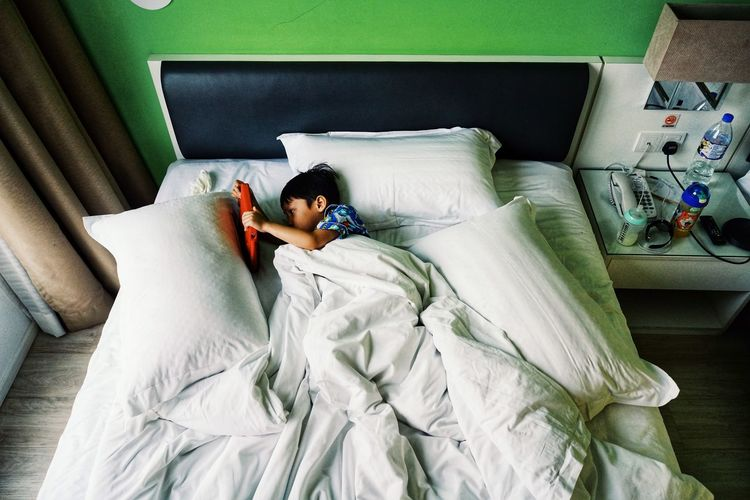 High angle view of boy resting on bed at home