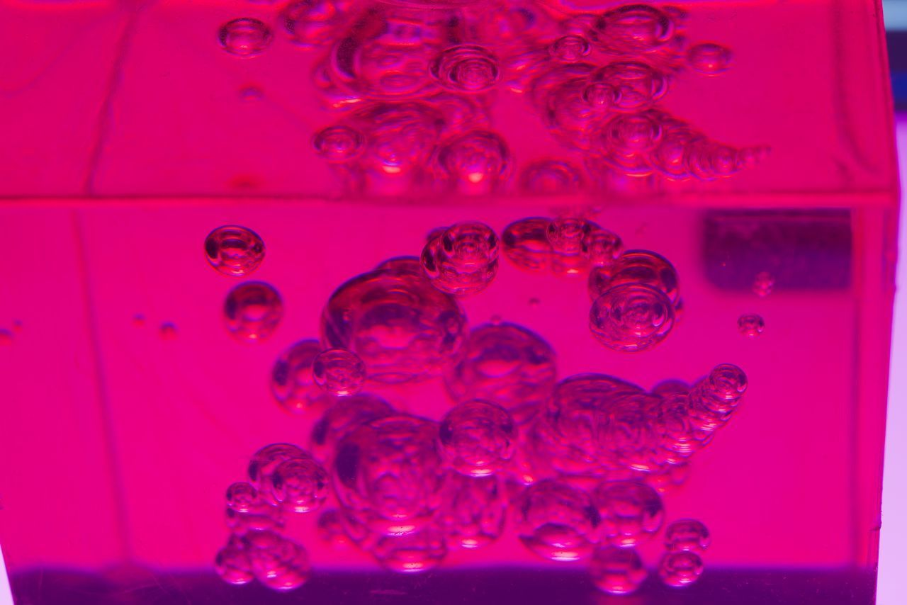 CLOSE-UP OF BUBBLES IN GLASS OVER WATER