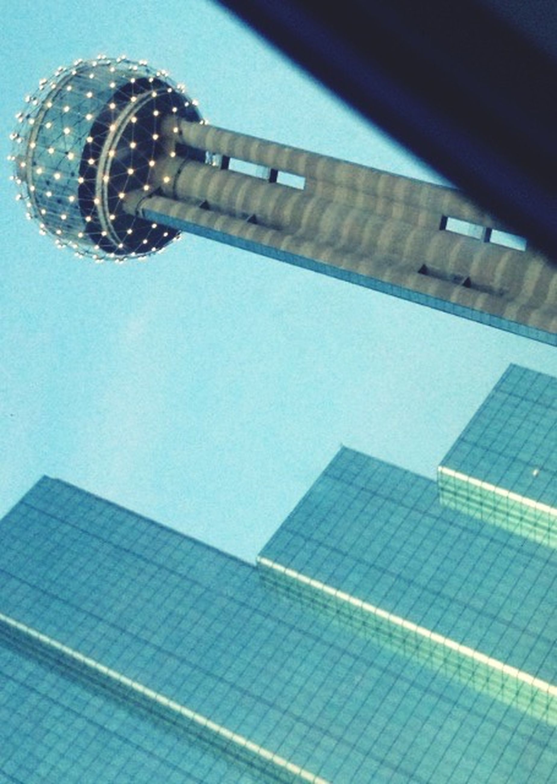 low angle view, building exterior, architecture, built structure, tall - high, tower, blue, modern, skyscraper, city, office building, sky, clear sky, no people, lighting equipment, outdoors, day, building, communications tower, glass - material