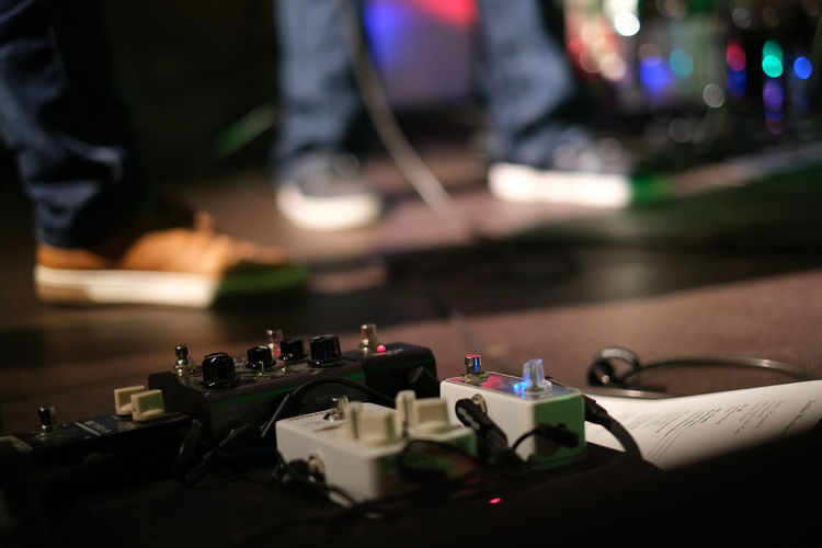 Close-up of effect pedals on stage during band concert
