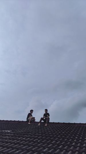 Low angle view of men on roof against sky