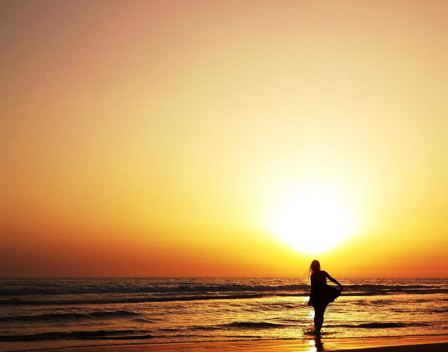 Silhouette woman standing on beach during sunset