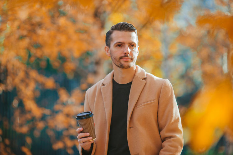 Portrait of young man standing outdoors during autumn