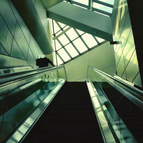 Low angle view of escalator against glass ceiling