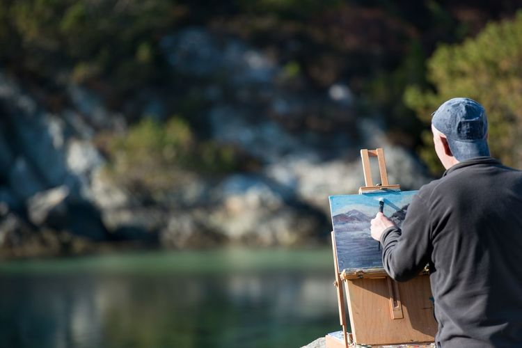 Man painting against lake