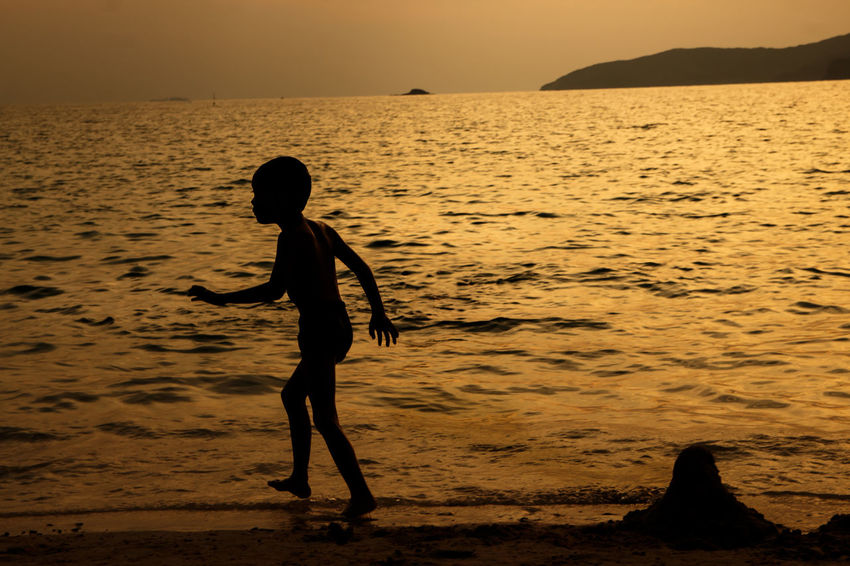 silhouette of people at the beach,The beauty of natural light at sunset. Sunset Water Sea Real People Land Beach Sky Silhouette Beauty In Nature Lifestyles One Person Leisure Activity Scenics - Nature Child Nature Childhood Horizon Over Water Orange Color Outdoors Silhouette Happiness Happy People Holiday Relaxing Children Women Man Romantic Orange Clouds And Sky Love Family Summer Sunrise Boy Freshair Freedom Fun