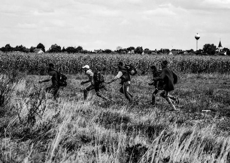 Refugees running on field