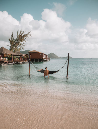 Man standing by hammock standing in sea