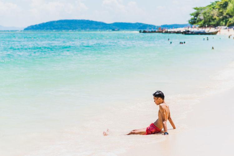Full length of man relaxing on beach