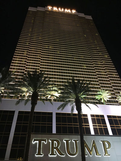 Las Vegas, NV, USA – November 13, 2016: Exterior shot of the Trump International Hotel in Las Vegas at night Las Vegas Trump Hotel Architecture Building Building Exterior Built Structure City Communication Hotel Illuminated Low Angle View Night No People Outdoors Palm Tree Plant Sky Text Tree Tropical Climate Trump Western Script Window