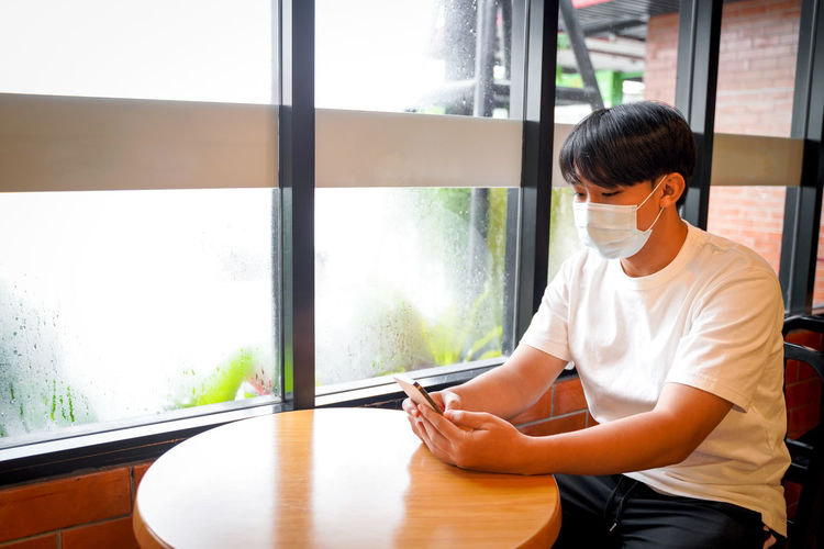 A handsome young teenage boy wear mask playing on smart mobile phone waiting in cafeteria.