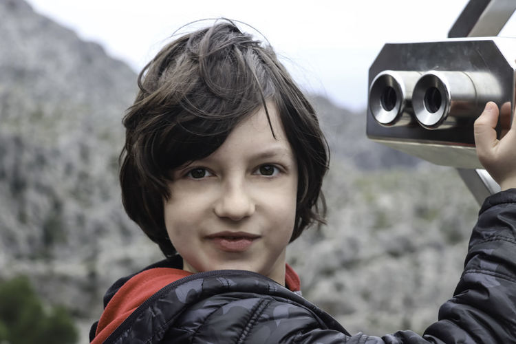 Portrait Of Boy Holding Coin Operated Binoculars