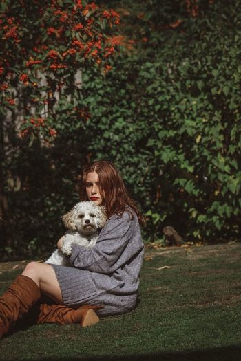 Portrait of young woman holding dog while sitting on grassy field against trees