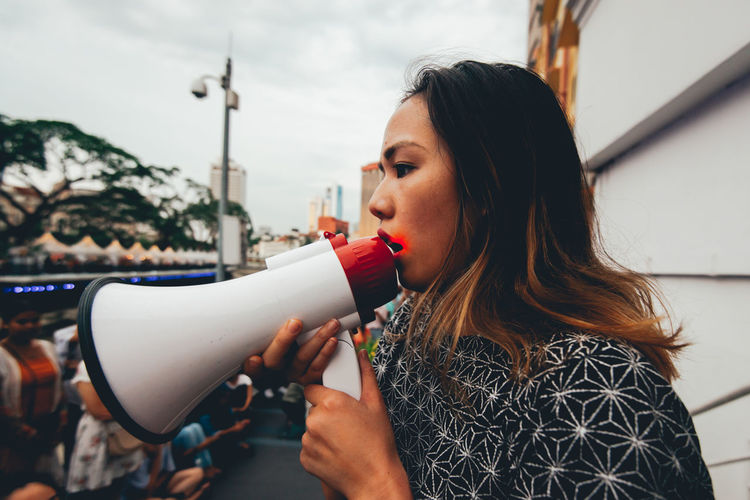 Woman holding megaphone while looking away against sky