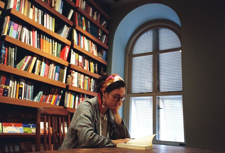 Woman reading book while sitting at table in library