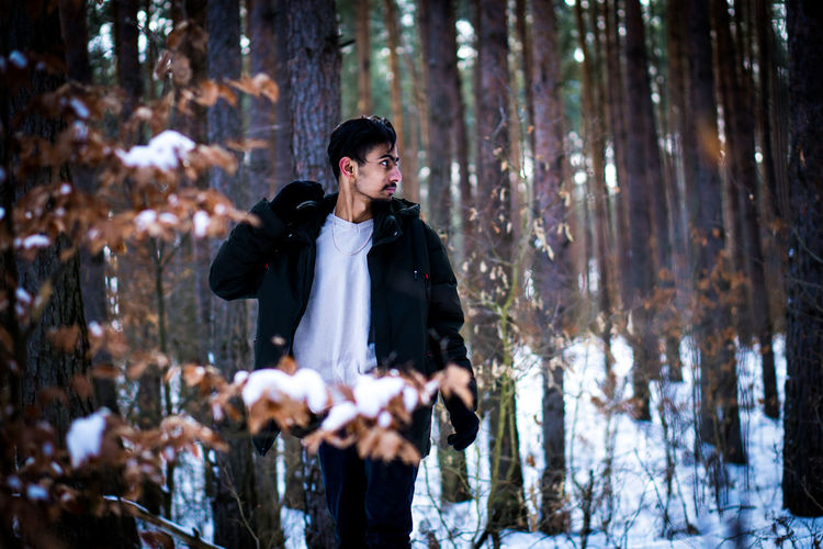 Young man standing in forest during winter