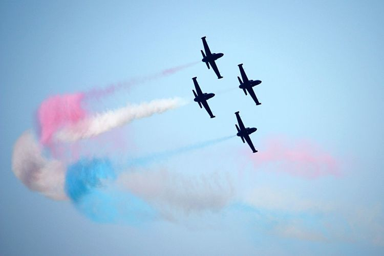 Low angle view of the silhouette fighter jets performing airshow