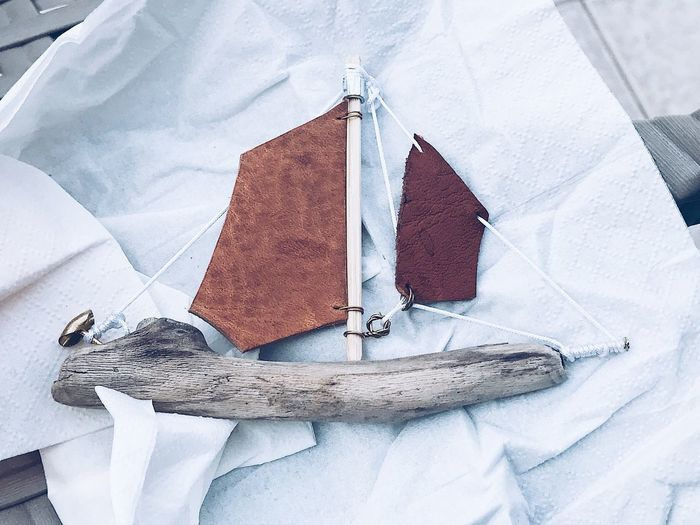 Sailing boat made of wood and leather Wooden Handmade Sail Sailing Boat Sailboat Sailing Ship Craft Product Craft Still Still Life Model Ship Leather Art Leather Craft Wood - Material Textile No People High Angle View Close-up Still Life White Color Indoors  Wood - Material Day Old Nature