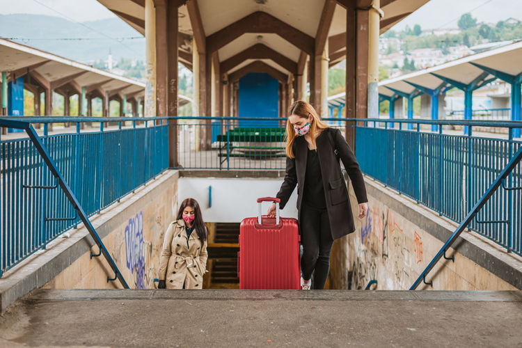 Young women wearing mask holding suitcase standing on staircase at railroad platform