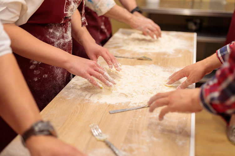 The hands of several people are kneading the dough on the table. mix a raw egg with flour.