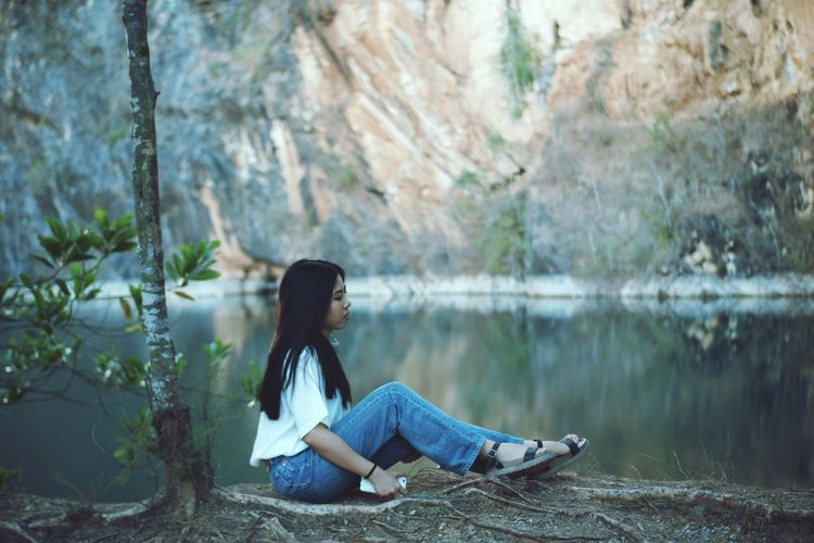 Side view of woman sitting by lake against rocks