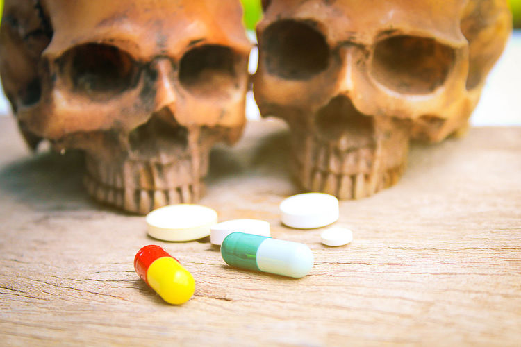 Close-Up Of Human Skull And Pills On Table
