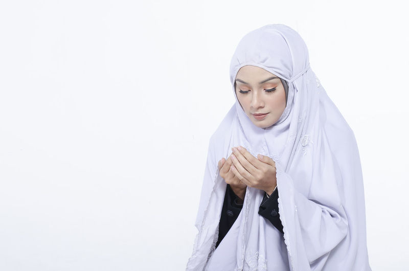 Woman In Traditional Clothing Praying Against White Background