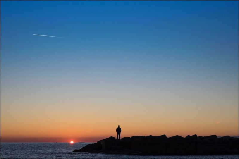 Silhouette Man Standing On Rocks By Sea Against Clear Sky During Sunset