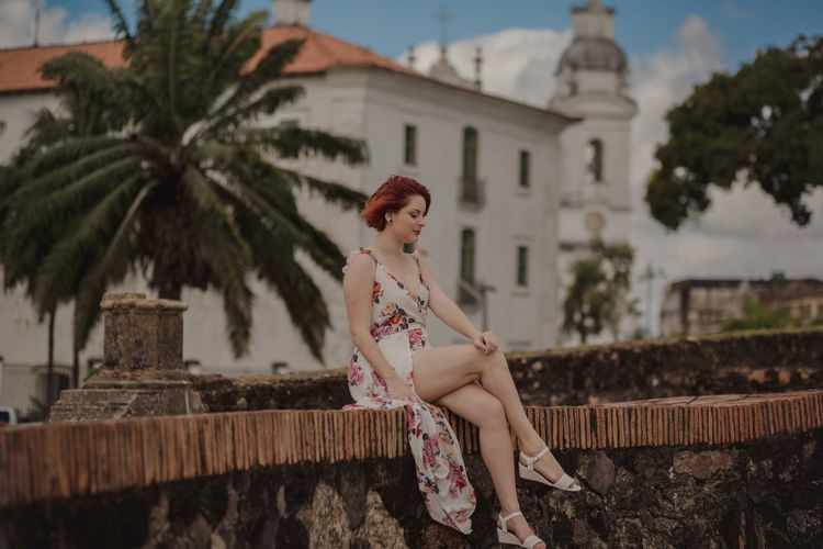 Woman looking away while sitting by tree against building