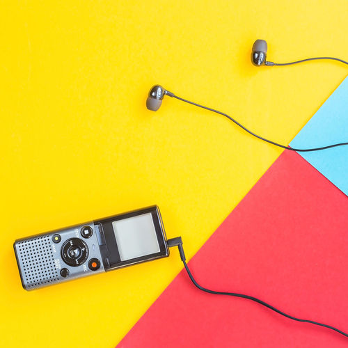 High angle view of recorder with headphones on colored background