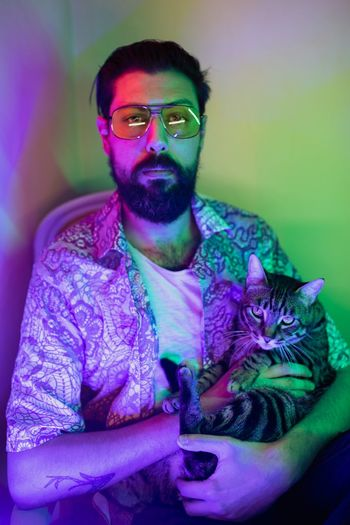 Shirt Cat One Person Glasses Front View Indoors  Young Adult Real People Young Men Sunglasses Lifestyles Leisure Activity Portrait Purple Casual Clothing Three Quarter Length Beard Adult Sitting Fashion Lumbersexual Personal Perspective Head And Shoulders Powder Paint Pink Color Blooming Body Paint Thoughtful Posing Surfer