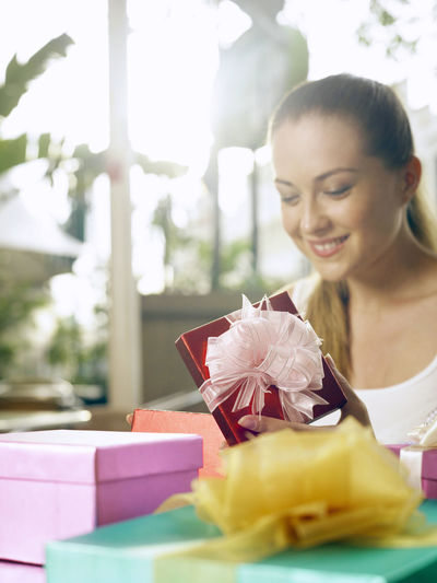 Smiling Woman Looking At Gifts In Restaurant
