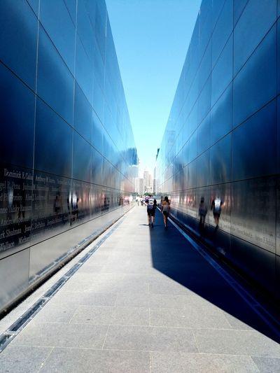 People walking in alley against blue sky