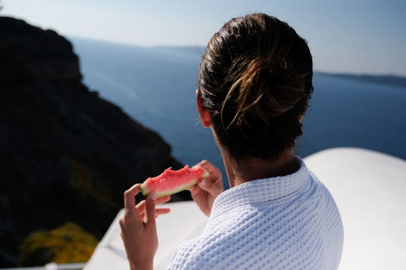 Close-up of woman having watermelon while looking at sea