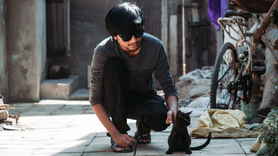 Young man holding cat while crouching outdoors