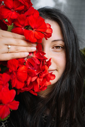 Close-up of woman holding red flower