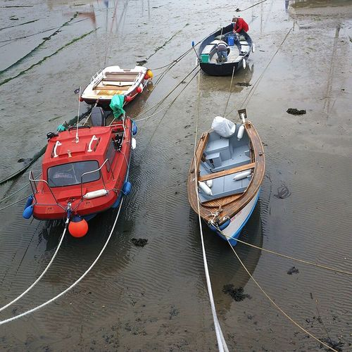 Motorboats Moored On Rippled Wet Sand