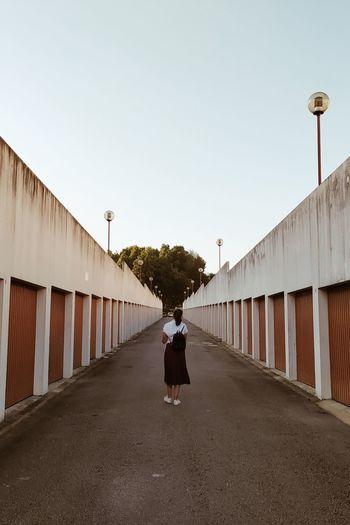 Rear view of woman walking on street against sky