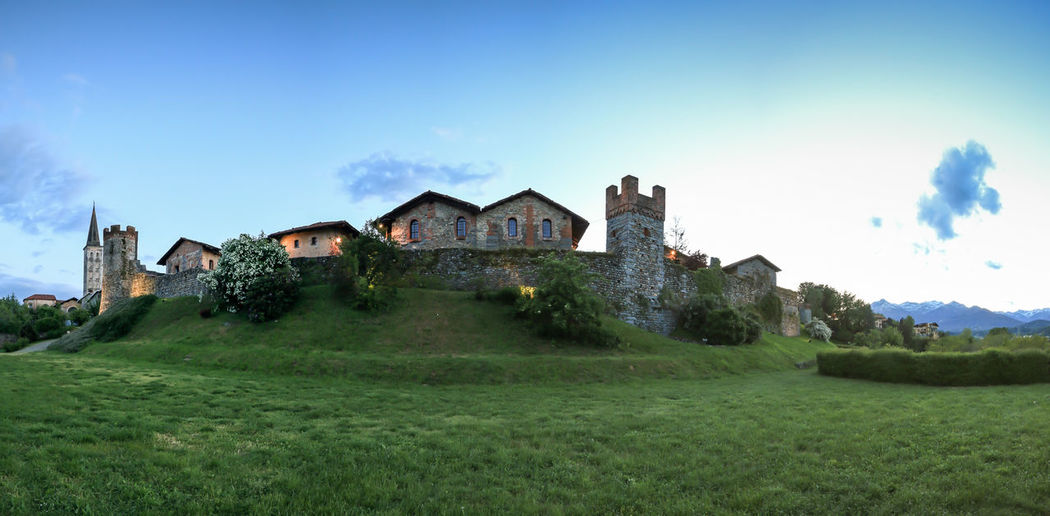 Candelo, Biella - May 4, 2016: Panoramic view of the Medieval village of Ricetto di Candelo in Piedmont, used as a refuge in times of attack during the Middle Age. Architecture Biella Blue Building Exterior Built Structure Candelo Candelo In Fiore Cloud Cloud - Sky Day Field Grass Grassy Green Color Growth Italy Landscape Lawn Medieval Village Nature No People Residential Building Residential Structure Ricetto Di Candelo  Sky