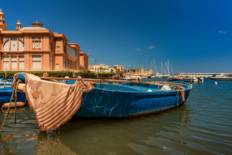 Boats Moored On Sea By Buildings Against Blue Sky