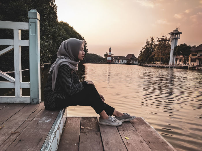 Woman sitting on railing by river against sky during sunset
