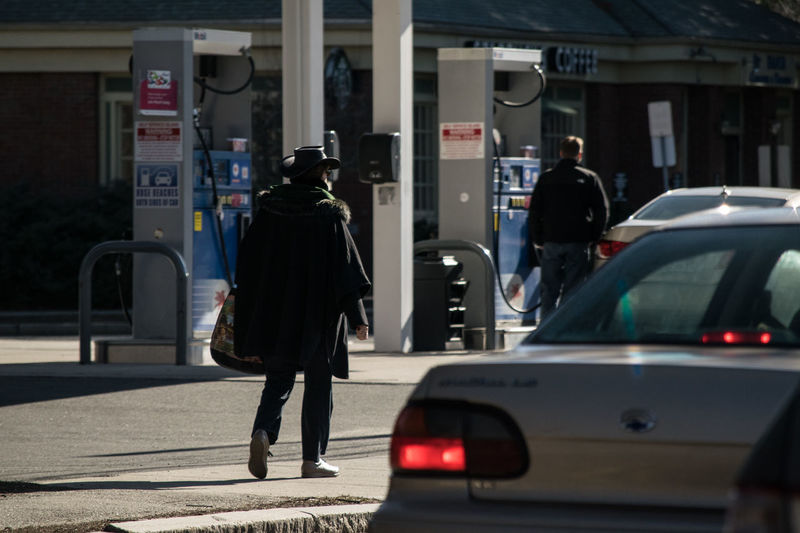 Rear View Of People By Cars At Gas Station
