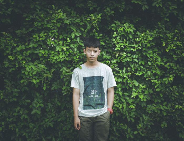 Portrait of boy standing against plants