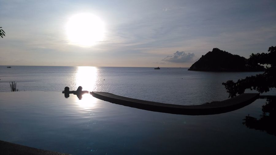 Silhouette couple in infinity pool by sea at sunset