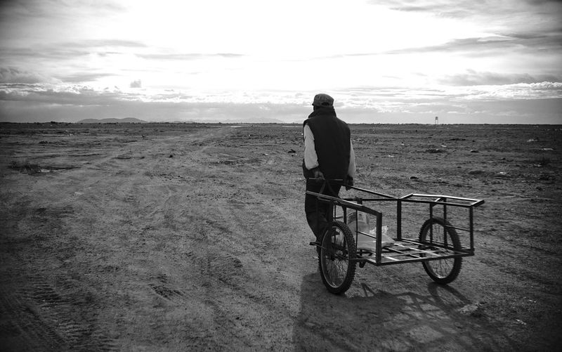 Man with bicycle standing on land