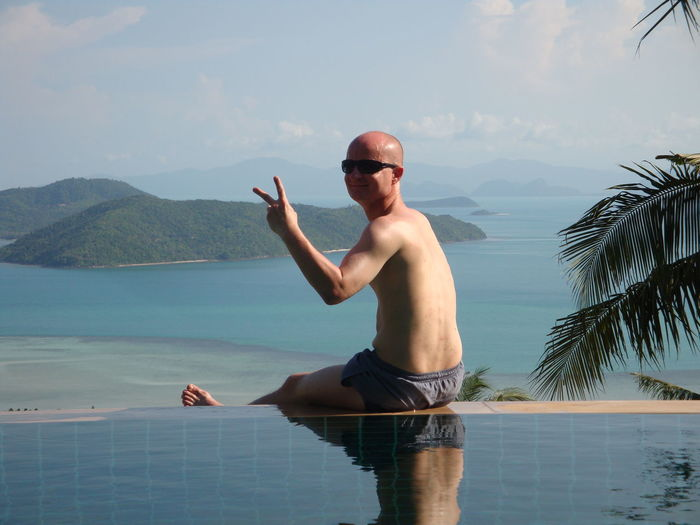 Portrait of smiling mature man showing peace sign at infinity pool against sea