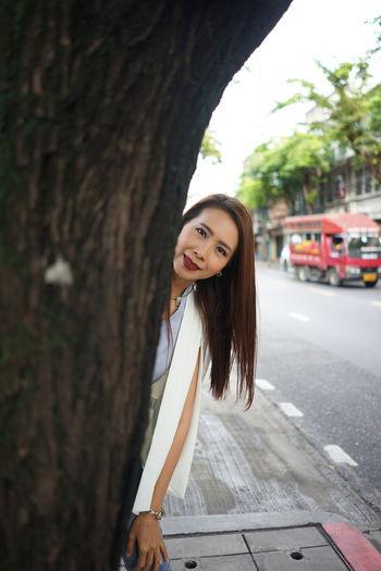Portrait of smiling woman standing behind tree on sidewalk