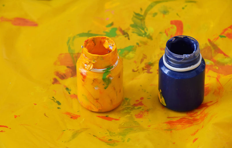 High angle view of yellow and blue paint bottles